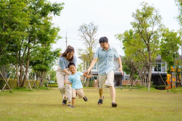 Azjatycka rodzina bawiąca się w łapanie na podwórku lub w publicznym parku w sąsiedztwie dla codziennego zdrowia i dobrego samopoczucia, zarówno fizycznego, jak i psychicznego szczęśliwej rodziny.