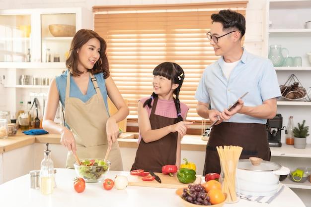 Azjatycka rodzina cieszy się gotowaniem razem sałatki w kuchni w domu.