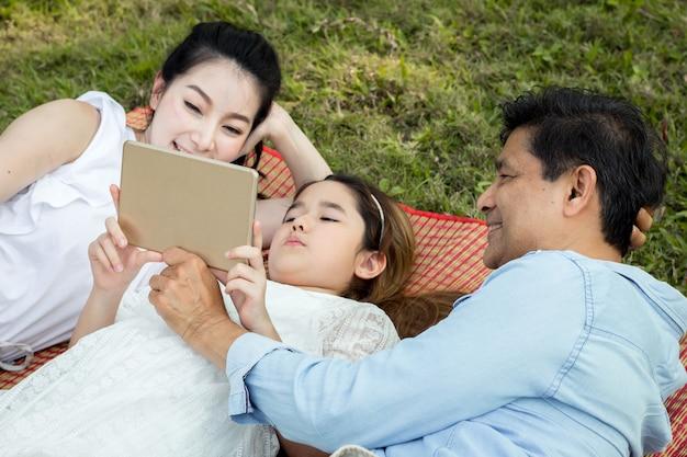 Azjatycka rodzina korzysta z tabletu na macie. dziewczyny uczą się z tabletu, którego uczą rodzice. rodzice i dzieci bawią się tabletem na macie w parku.