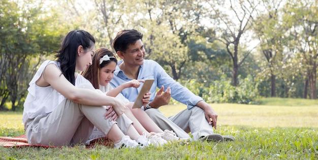 Azjatycka rodzina korzysta z tabletu na macie. dziewczyny uczą się z tabletu, którego uczą rodzice.