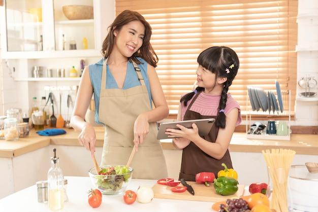 Azjatycka rodzina, matka i córka gotują razem przygotowują sałatkę w kuchni w domu.