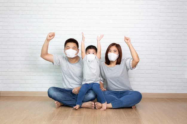 Azjatycka rodzina nosi ochronną maskę medyczną w celu zapobiegania wirusowi covid-19 i wręcza w górę i siedzi razem na podłodze w domu. ochrona rodziny przed zanieczyszczonym powietrzem