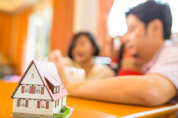 Azjatycka rodzina oszczędza pieniądze do skarbonki w domu.
