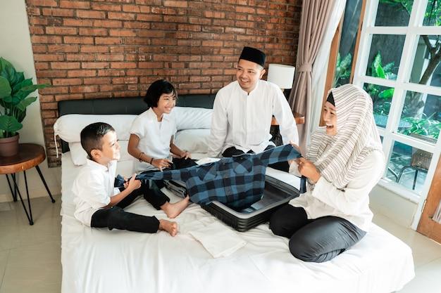 Azjatycka rodzina przygotowuje ubrania i wkłada do walizki