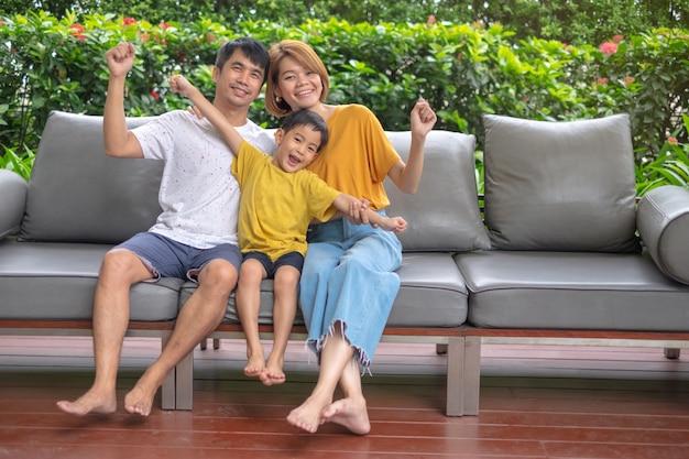 Azjatycka rodzina relaksuje na kanapie przy plenerowym