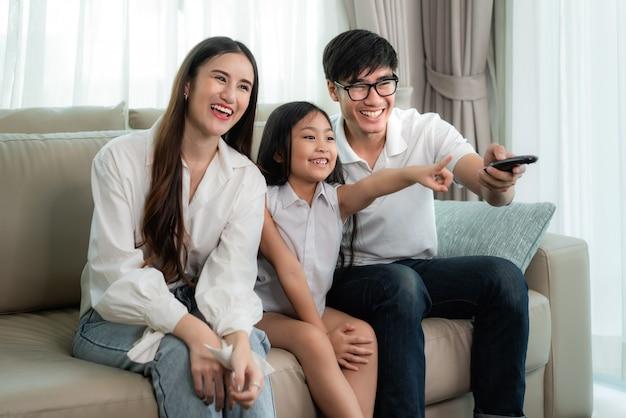 Azjatycka rodzina siedzi i ogląda telewizję oraz uśmiecha się podczas oglądania zabawnego programu w telewizji.