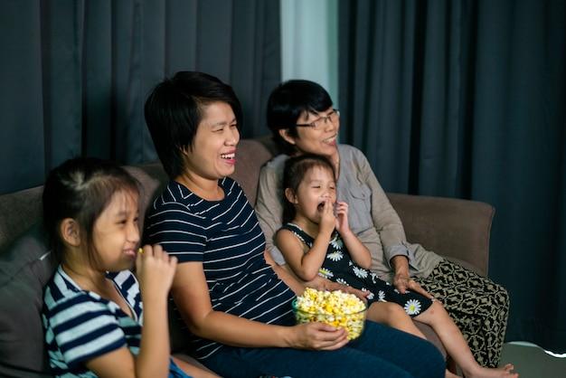 Azjatycka rodzina siedzi na wygodnej sofie i je popcorn podczas oglądania filmu w salonie w domu. domowa rozrywka, azjatycka rodzina i koncepcja czasu razem