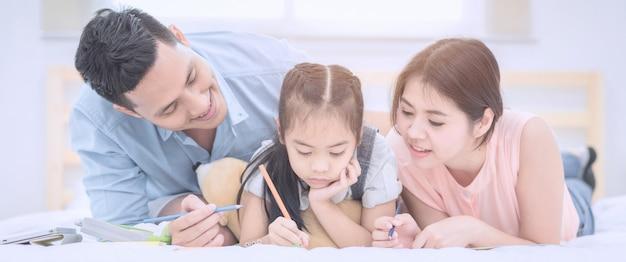 Azjatycka rodzina szczęśliwa ono uśmiecha się i relaksuje na łóżku w domu.
