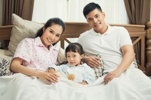 Azjatycka rodzina uczy dzieci czytać książki w łóżku