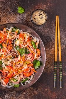 Azjatycka sałatka z makaronem ryżowym, krewetkami i warzywami, widok z góry.
