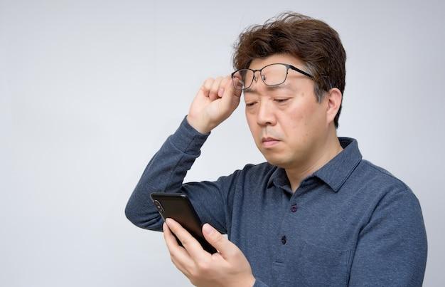Azjatycka samiec próbuje czytać coś na jego telefonie komórkowym. słaby wzrok, starczowzroczność, krótkowzroczność.