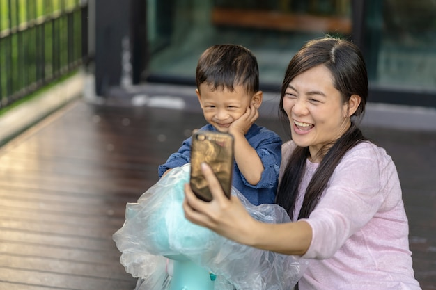 Azjatycka samotna mama z synem jest razem selfie, gdy mieszka w domu do samodzielnej nauki lub do domu