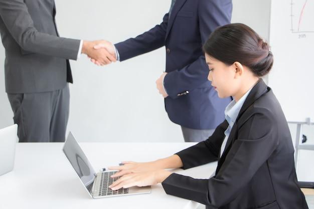 Azjatycka sekretarka ubrana w formalny strój pisała na laptopie notatkę ze spotkania. z tyłu biznesmeni i dłonie zacisnęli w sali konferencyjnej umowę.