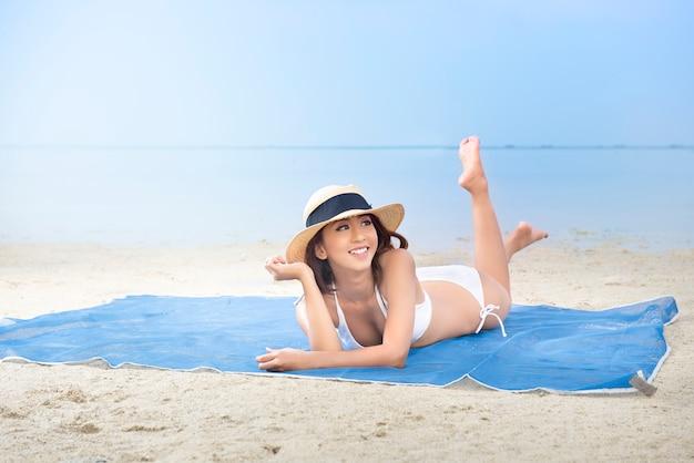 Azjatycka seksowna dziewczyna w bikini i kapeluszu kłama na dywanie w plaży