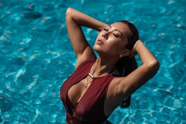 Azjatycka seksowna kobieta w burgundowym bikini przy pływackim basenem w słonecznym dniu, jasny ton, moda bikini poza