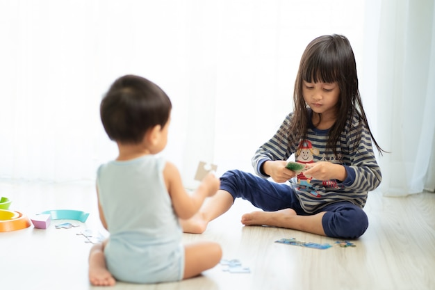 Azjatycka siostra gra puzzle ze swoim młodszym bratem, pojęcie więzi z rodzeństwem