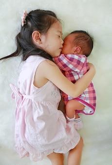 Azjatycka siostra i nowonarodzona chłopiec śpi wpólnie na białym futerkowym tle.