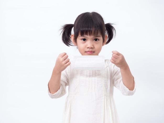 Azjatycka śliczna 4-letnia dziewczynka ubrana w higieniczną maskę ochronną rozprowadza wirusa korony covid-19 na zimną grypę lub zanieczyszczenia na białej ścianie.