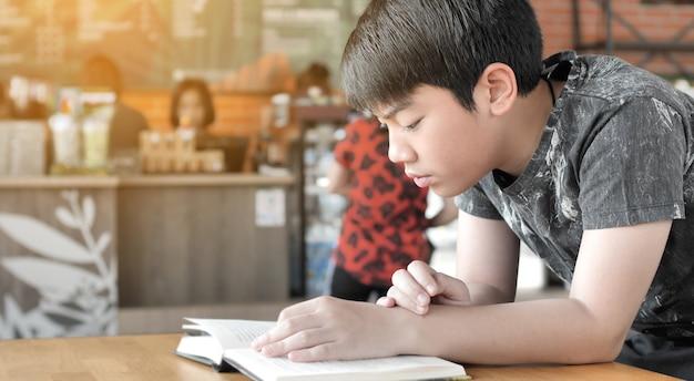 Azjatycka śliczna chłopiec czyta książki podczas gdy czeka na ich matki kupować napoje w kawiarni.