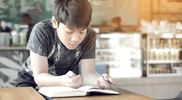 Azjatycka śliczna chłopiec czyta książki w kawiarni.