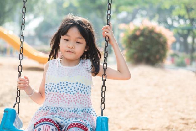 Azjatycka śliczna dziewczyna ma zabawę i szczęśliwy na huśtawce w boisku, jest szczęśliwa i przyjemna na jej wakacje