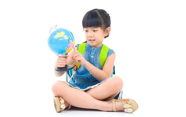 Azjatycka śliczna dziewczyna patrzeje kulę ziemską