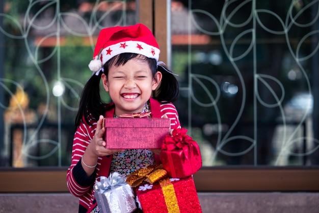 Azjatycka śliczna dziewczyna z podekscytowaniem otrzymuje świąteczny prezent
