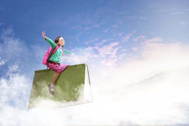 Azjatycka śliczna dziewczyna z szkłami i plecaka obsiadaniem na książce z niebieskim niebem