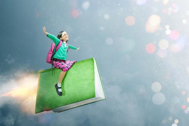 Azjatycka śliczna dziewczyna z szkłami i plecaka obsiadaniem na książce