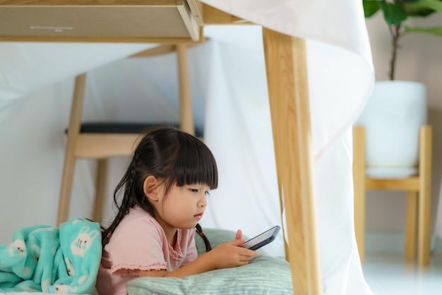 Azjatycka śliczna mała dziewczynka ogląda kreskówkę w smartfonie