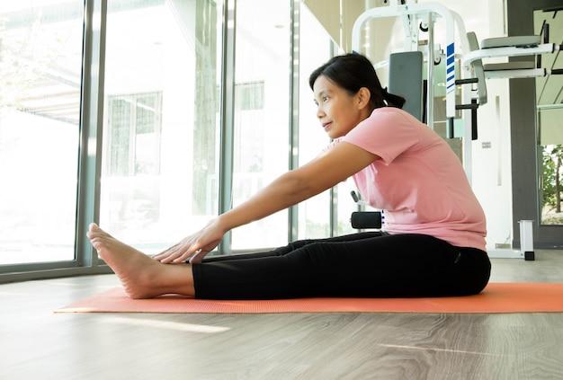 Azjatycka sprawności fizycznej kobieta rozgrzewka przed ćwiczy w gym, kobieta w średnim wieku pracuje joga