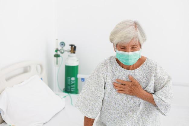 Azjatycka stara cierpliwa kobieta z maskową chorobą w sala szpitalnej z wirusową grypą