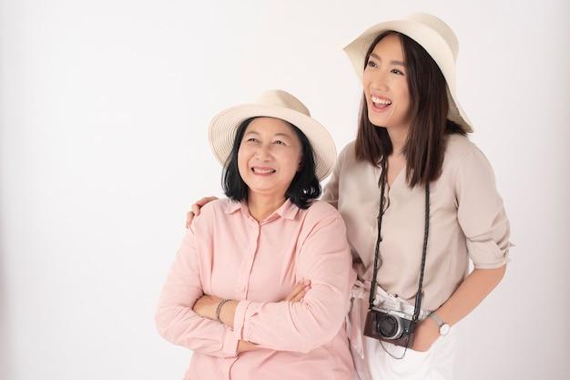 Azjatycka stara kobieta i jej córka na biel ścianie