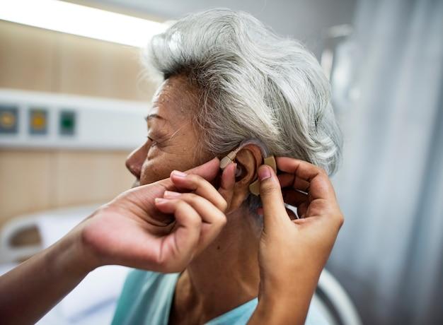 Azjatycka stara kobieta ma jej ucho sprawdzać