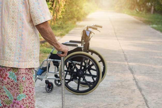 Azjatycka starej kobiety pozycja z jego rękami na chodzącym kiju