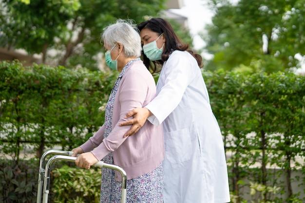 Azjatycka starsza kobieta chodzi z chodzikiem i nosi maskę na twarz w celu ochrony przed koronawirusem covid19