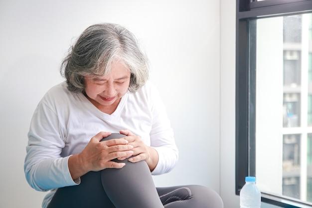 Azjatycka starsza kobieta ćwicząca w domu kontuzja prawego kolana jest dużo bólu. koncepcja opieki zdrowotnej dla seniorów. skopiuj miejsce