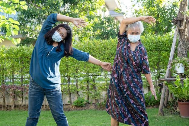 Azjatycka starsza kobieta ćwiczy pacjenta ze szczęśliwym świeżym cieszyć się w parku