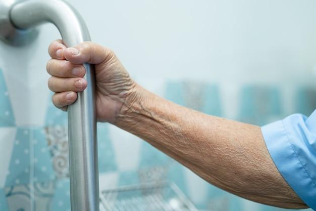 Azjatycka starsza kobieta korzysta z zabezpieczenia uchwytu pomostu na zboczu