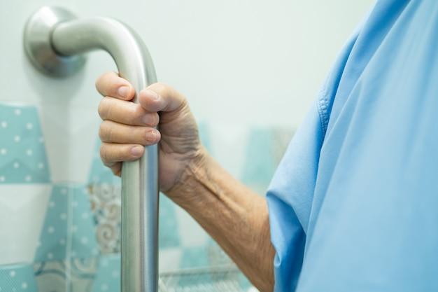 Azjatycka starsza kobieta korzysta ze stoku chodnika z zabezpieczeniem w toalecie