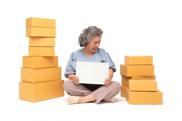 Azjatycka starsza kobieta małego biznesu początkowy niezależny z pakuneczka pudełkiem i komputerowym laptopem i obsiadaniem na podłoga odizolowywającej na biel ścianie, online marketingu pakowania pudełka dostawy pojęcie