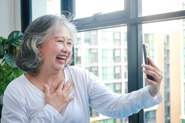 Azjatycka starsza kobieta mieszka w domu, trzymając smartfon online, rozmawiając z wnukami. dystans społeczny podczas pandemii koronawirusa. nauka technologii komunikacji dla osób starszych
