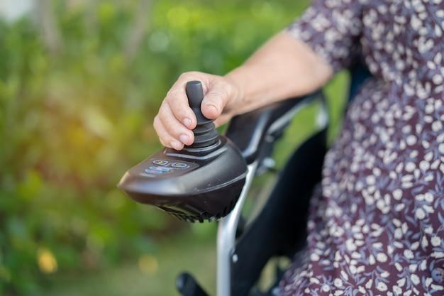 Azjatycka starsza kobieta na elektrycznym wózku inwalidzkim na oddziale szpitala pielęgniarskiego