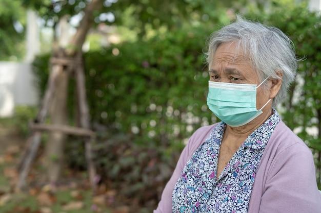Azjatycka starsza kobieta nosząca maskę na twarz w celu ochrony koronawirusa covid-19.