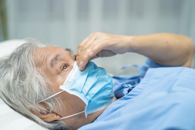 Azjatycka starsza kobieta pacjent jest ubranym maskę w szpitalu dla ochrony coronavirus covid-19 wirus.