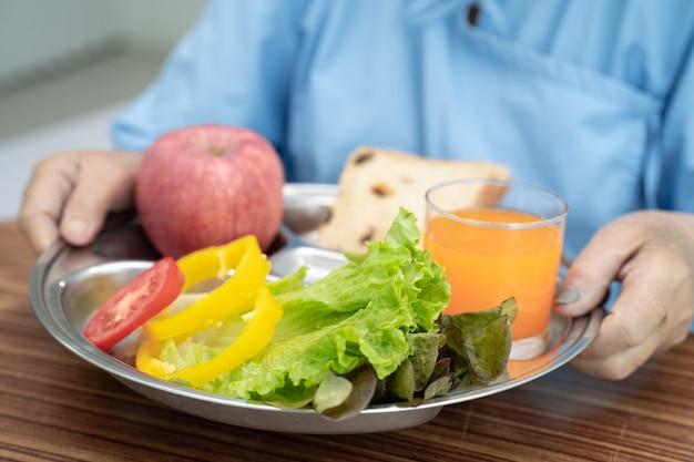 Azjatycka starsza kobieta pacjentka je śniadanie warzywo zdrowa żywność