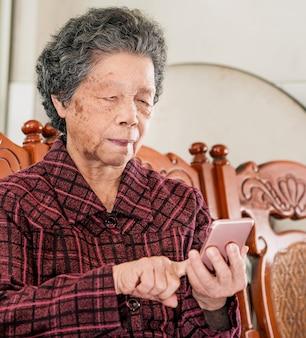 Azjatycka starsza kobieta siedzi i patrząc na smartfonie