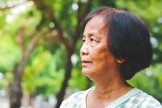 Azjatycka starsza kobieta stojąca w ogrodzie czuje się szczęśliwa. starszy koncepcja opieki zdrowotnej szczęśliwego życia na emeryturze. społeczność seniorów. skopiuj miejsce