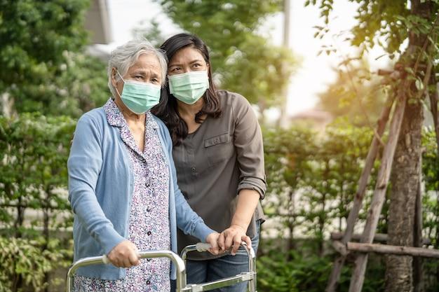 Azjatycka starsza kobieta ubrana w maskę na twarz w parku w celu ochrony koronawirusa covid-19.