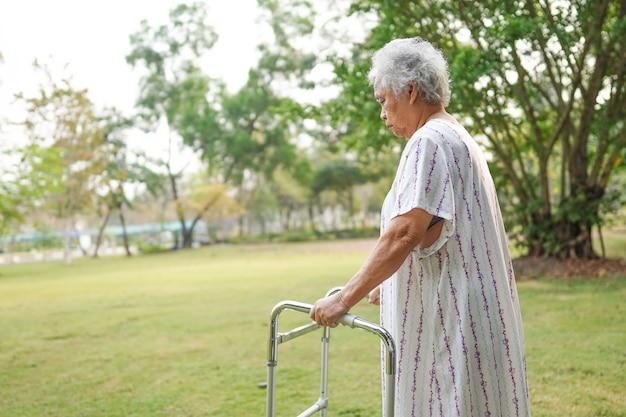 Azjatycka starsza kobieta używa piechura podczas gdy chodzący przy parkiem.